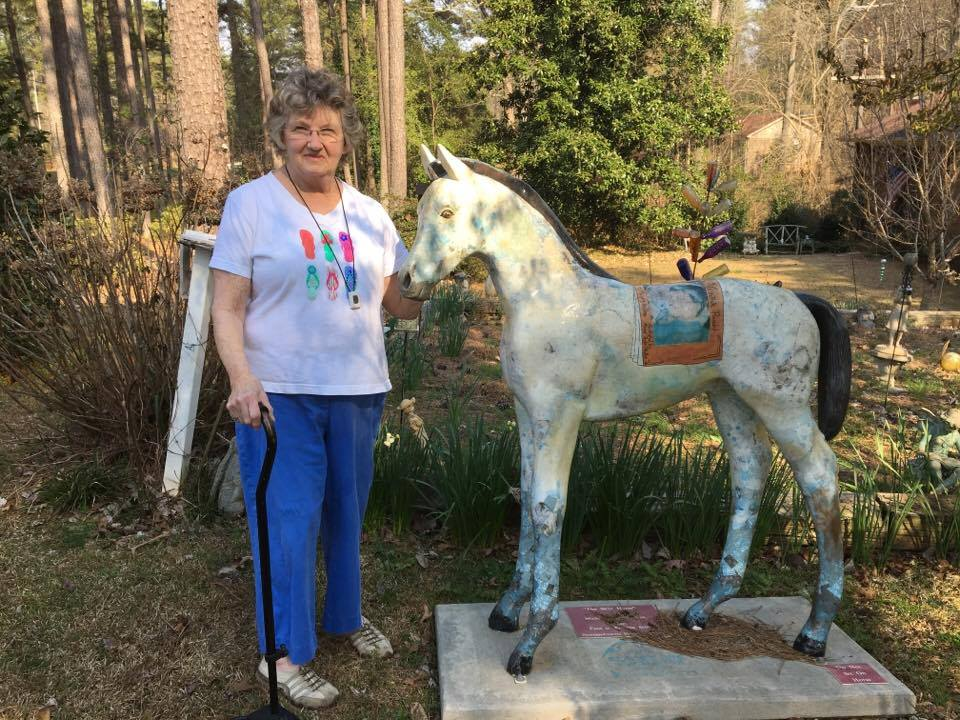 Earlene Scott stands beside a horse sculpture in her garden.