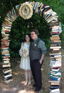 Josh & Megan under the fantastic book archway at their wedding, made by local craftspersonForrestWorks. May 2014